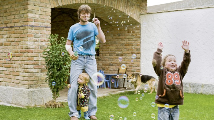 Markus with Michelangelo hand prosthesis blowing soap-bubbles into the air to entertain his children.