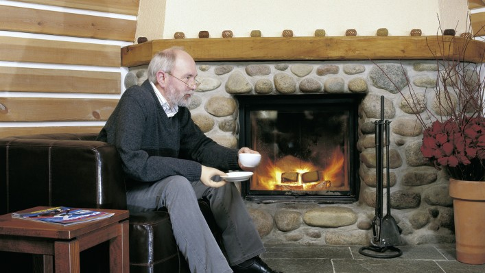 Man drinks a cup of coffee by the fireplace