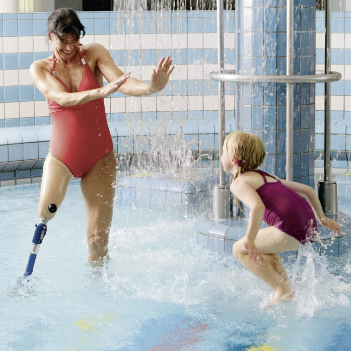 Woman uses her Aqualine water-resistant knee to play in the pool with her daughter.