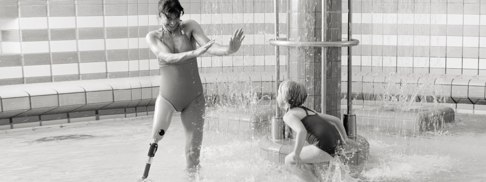 Mother and daughter playing in wading pool at water park.