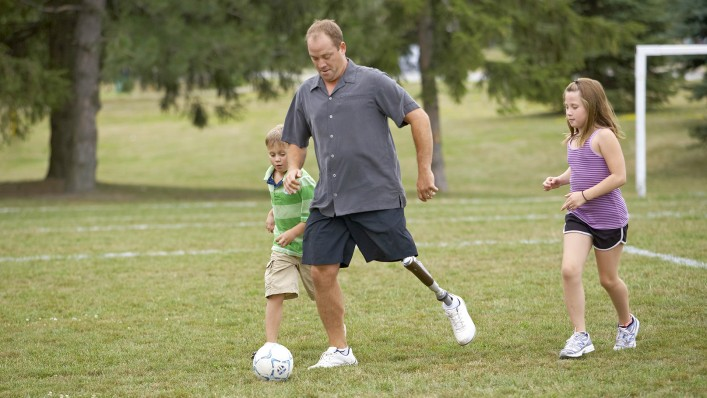 Jonathan with C-Leg prosthesis playing soccer with his children.