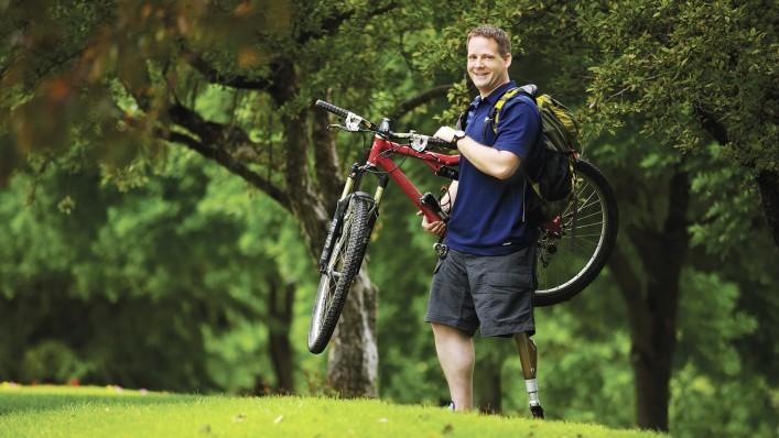 Matt with C-Leg prosthesis carrying his bike above the lawn.