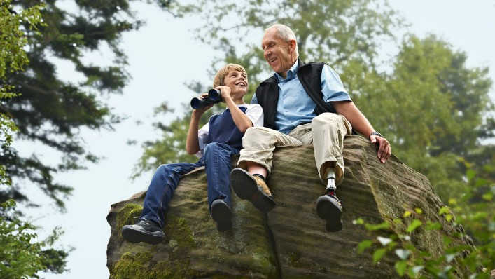 Peter with C-Leg prosthesis sitting on a rock with his grandchild.