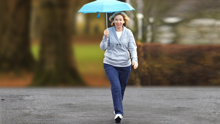 User with C-Leg prosthesis walking in the rain with an umbrella.