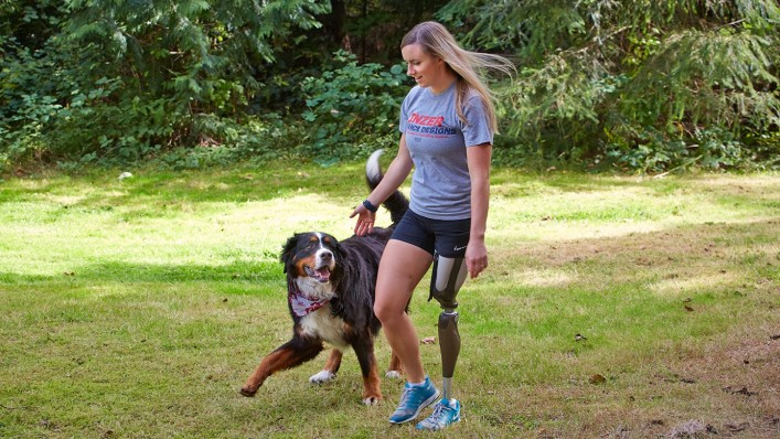 Ali walking with her dog while using her Genium knee