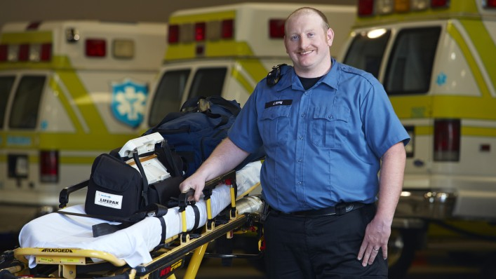 Joel with Genium standing next to an ambulance stretcher.