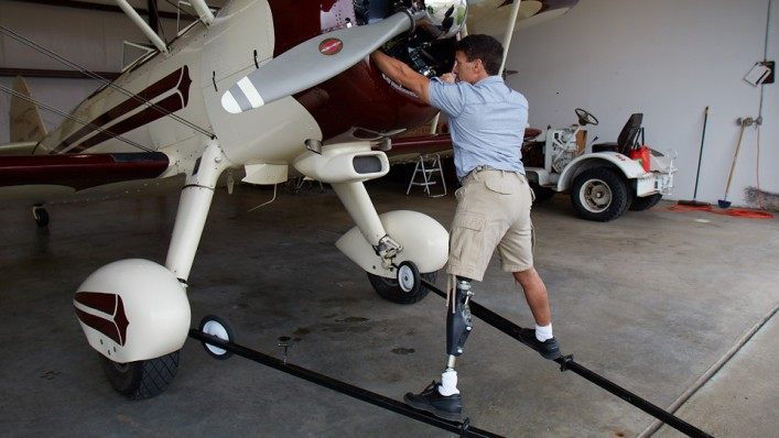 Andrew uses his Genium X3 prosthetic leg to work on his plane.
