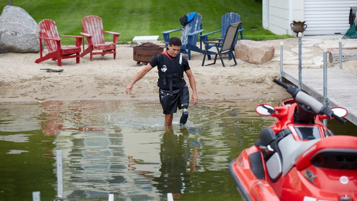 Andrew wading in the lake using his waterproof Genium X3 prosthetic leg.