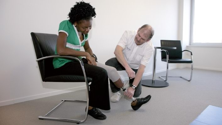Therapist helps to adjust the upper limb prosthesis.
