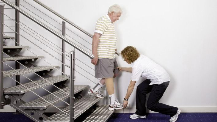 Therapist explains the rehabilitation exercise how to go down stairs.