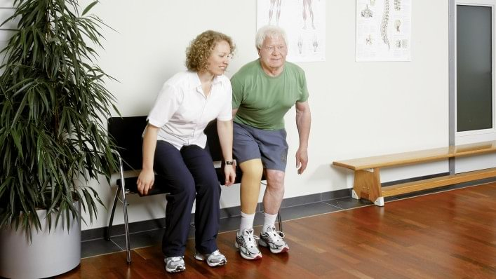 Therapist explains the rehabilitation exercise how to sit down.