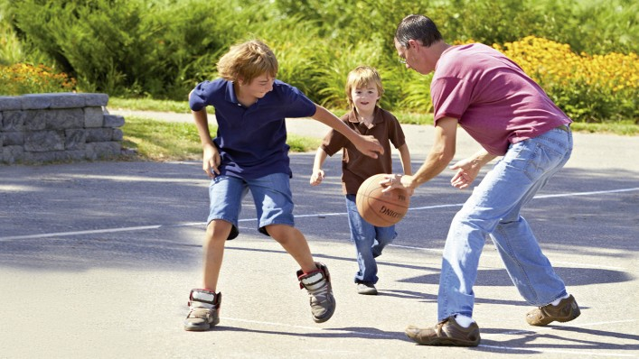 Rick with Harmony prosthesis playing basketball with his children.