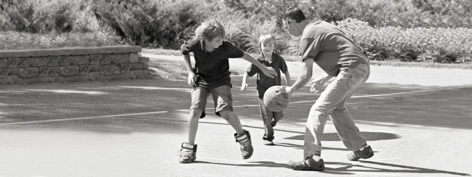 Rick with lower limb prosthesis playing basketball with his children.