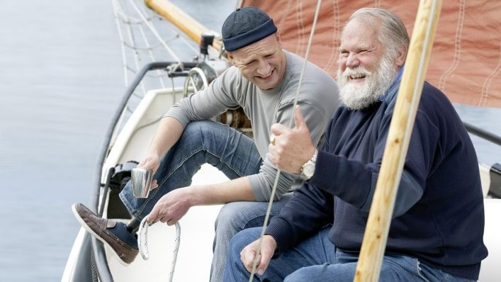 Carsten with Harmony prosthesis sitting next to a man on his sail boat.