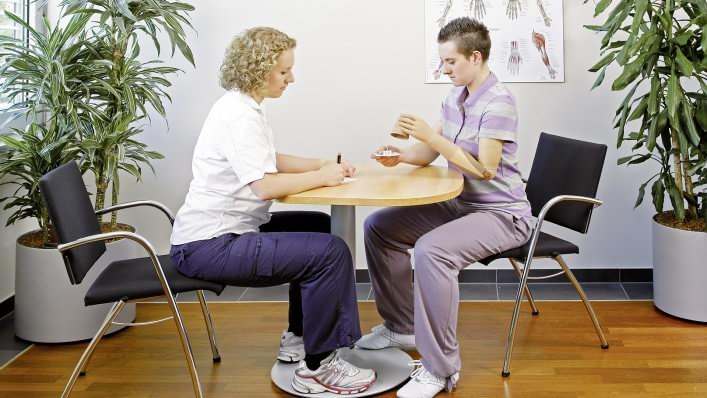 Therapist explains how to use little games to advance the skills to handle the prosthesis.