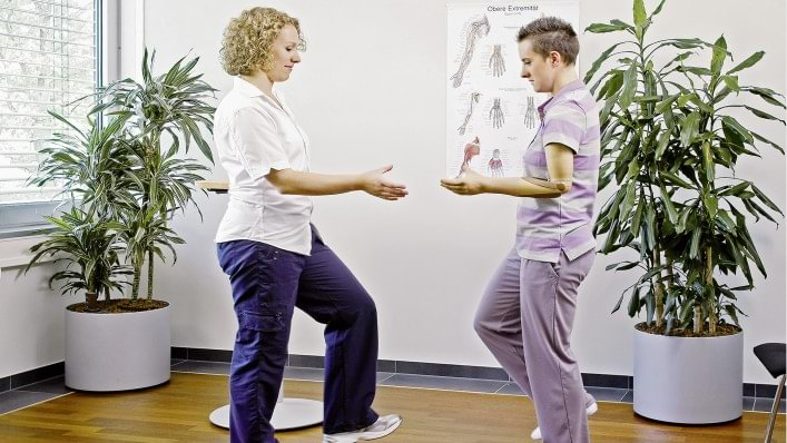 Therapist explains how to concentrate on body balance and using the prosthesis at the same time.