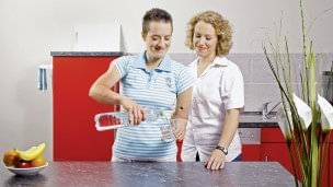 Therapist explains the rehabilitation exercise for activities of daily life - pouring water in a glass